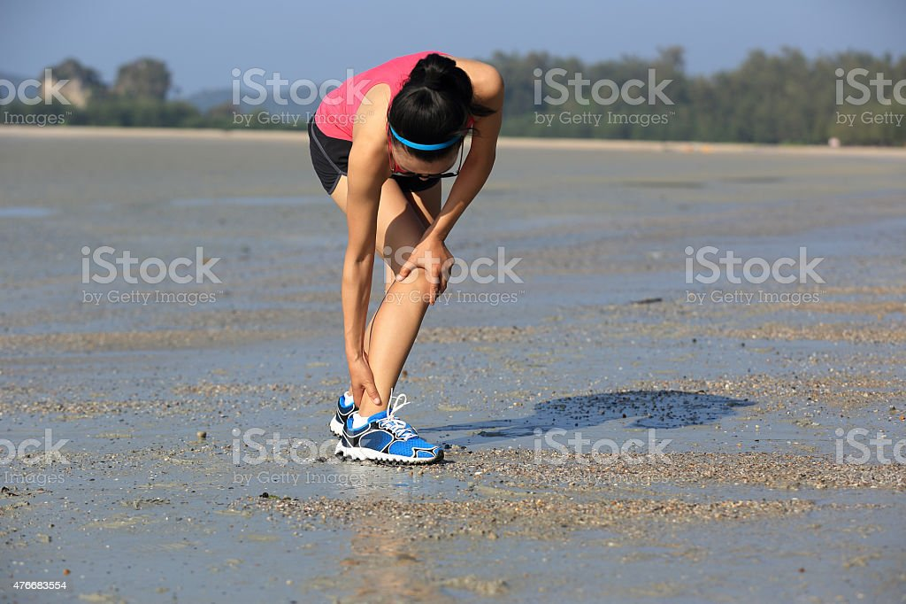 woman runner hold her twisted ankle stock photo