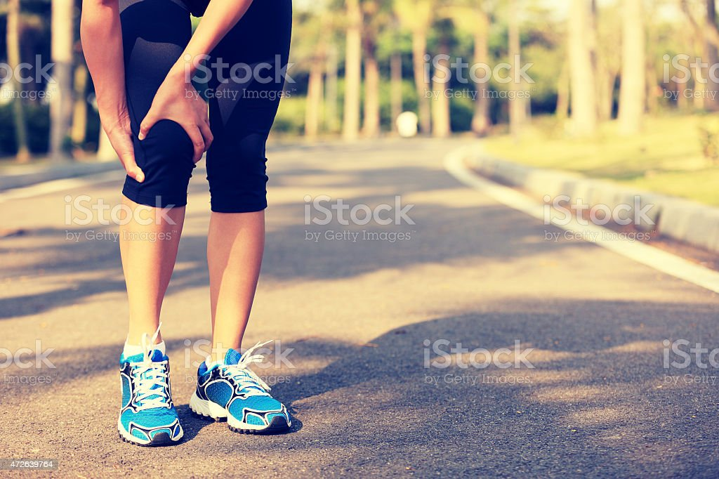 woman runner hold sports injured leg on tropical park trail stock photo
