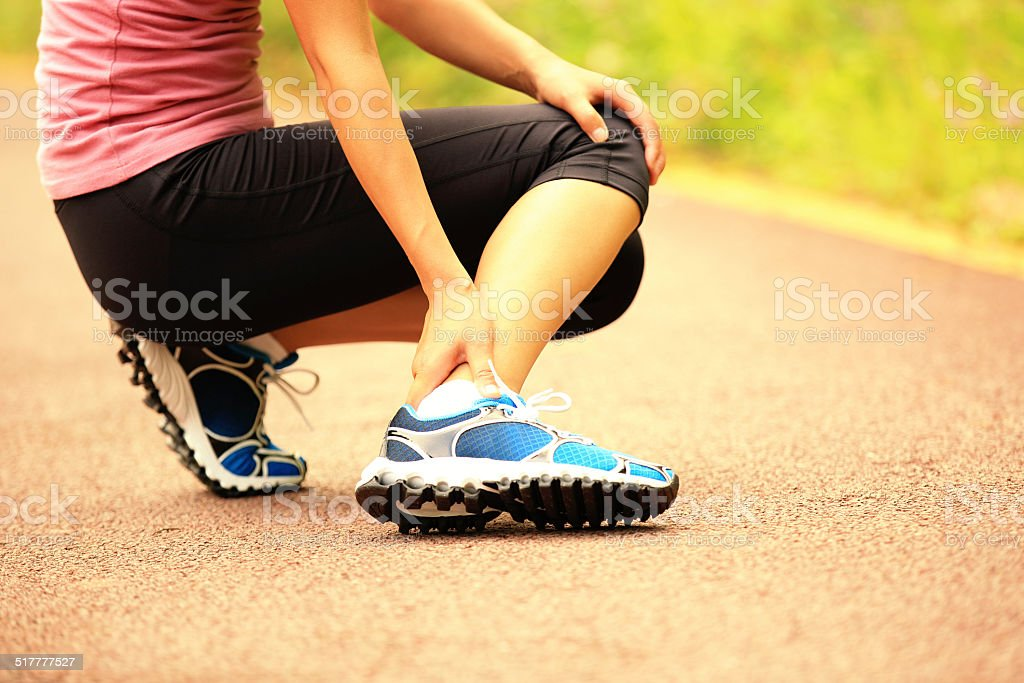 woman runner hold twisted ankle stock photo