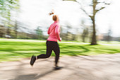 Young woman in sportswear, jogging in London on a sunny day. Stretching before her run. Running in the park early in the morning.