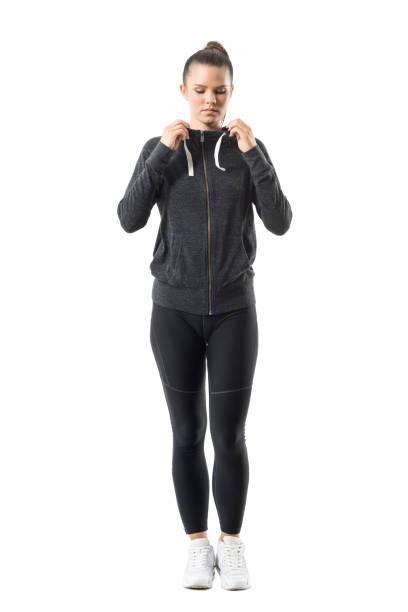 Woman runner in zip up hoodie sweatshirt get ready for running looking down stock photo