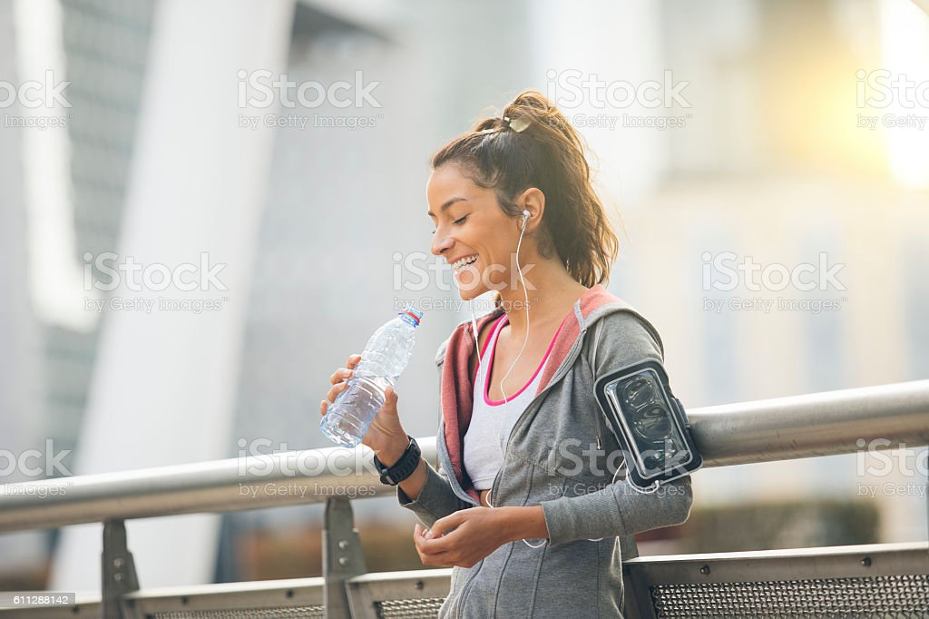 Woman runner is having a break and drinking water stock photo
