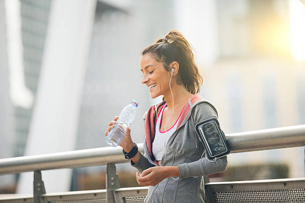 woman runner is having a break and drinking water - armband water stock-fotos und bilder
