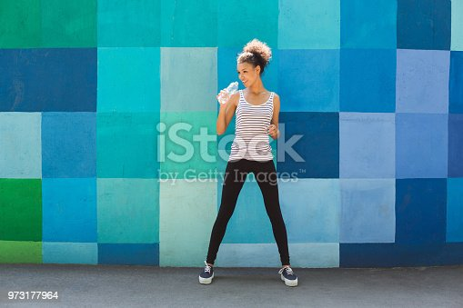 Young african-american woman runner is having break, drinking water while jogging in city, copy space