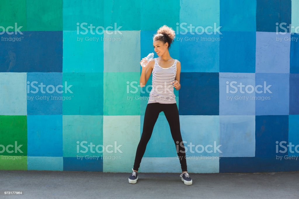 Woman runner is having break, drinking water stock photo
