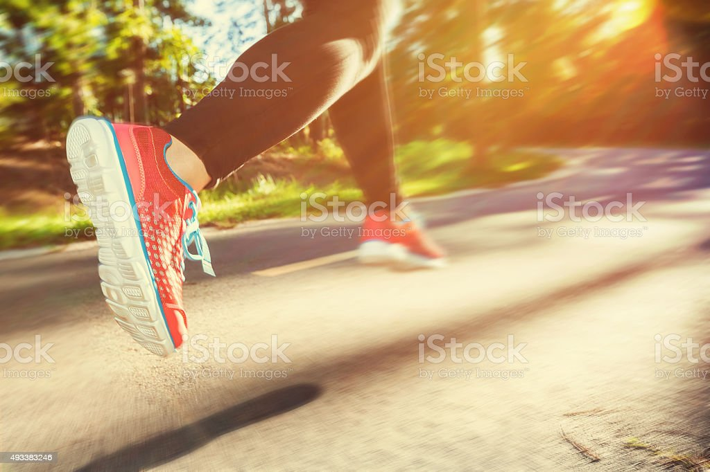 Woman runner jogging down an outdoor trail stock photo