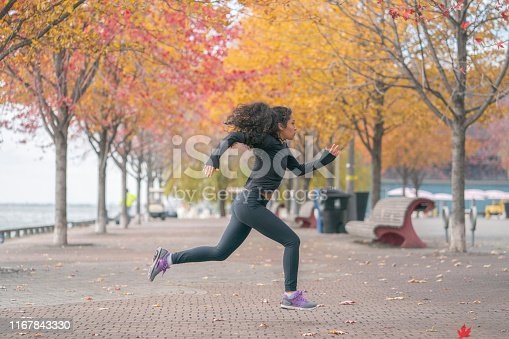 A woman of african descent runs through the park on a chilly autumn day.