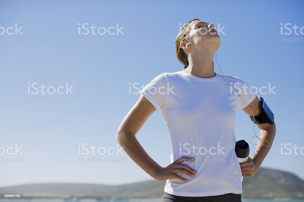 Woman runner relaxing and listening to mp3 player royalty-free stock photo