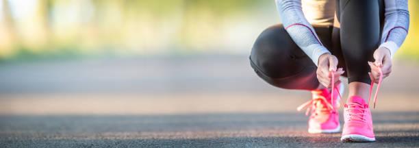läuferin, die schnürsenkel bindet, bevor sie im herbstbaumallee park joggen. sport weibliche herbst outfit leggins und thermische unterwäsche. - joggerin stock-fotos und bilder