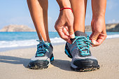 istock Woman runner tying shoelaces on the beach. 490072790