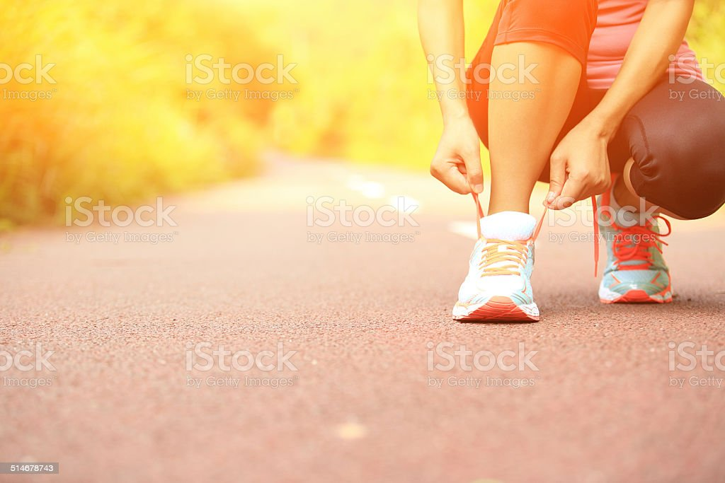 woman runner tying shoelaces on trail stock photo