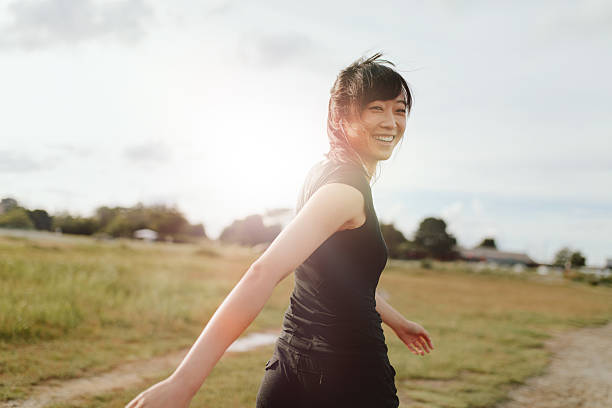 Woman runner walking on field in morning Outdoor shot of smiling young woman runner looking at camera. Chinese female walking on field in morning. looking over shoulder stock pictures, royalty-free photos & images