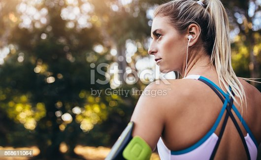 Close up shot of a female athlete wearing earphones and a mobile phone fixed on an arm band. Woman listening to music during workout.
