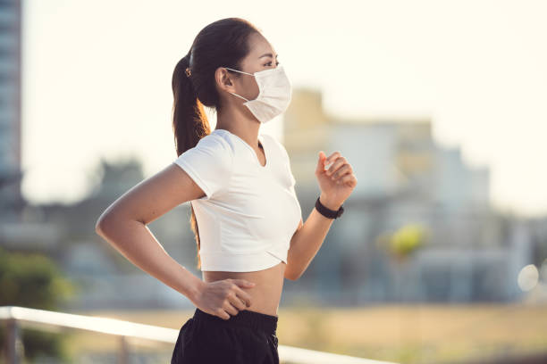 Woman runners morning exercise she wears a nose mask. Protection against dust and viruses stock photo