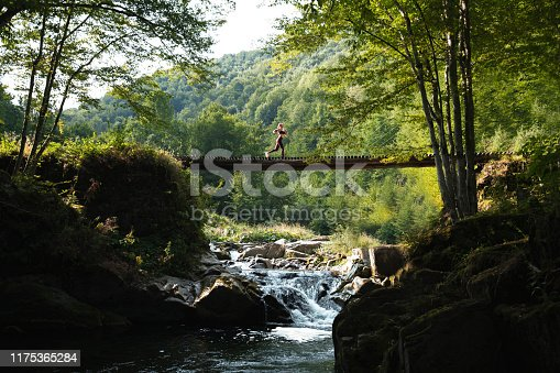 Woman running across bridge in nature.