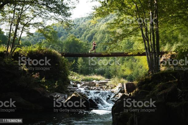 Photo of Woman running across bridge in nature.