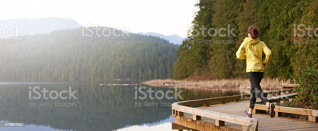 Woman running along a wooden lakeside path stock photo