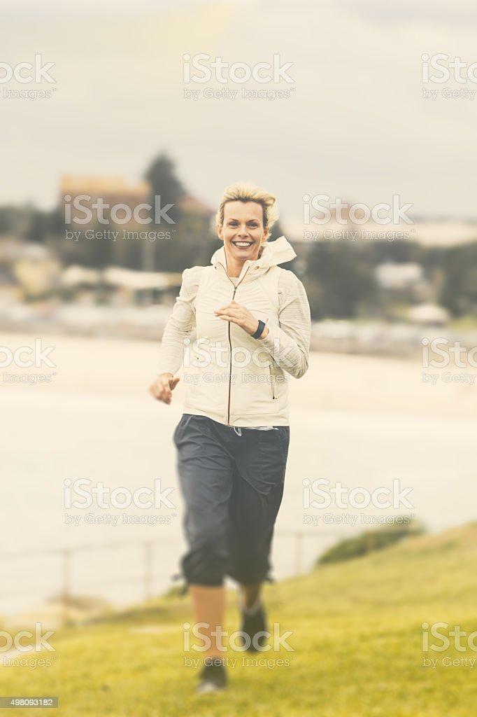 Woman running along famous bondi beach sydney australia stock photo