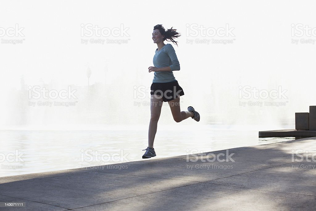 Woman running along lake in park royalty-free stock photo