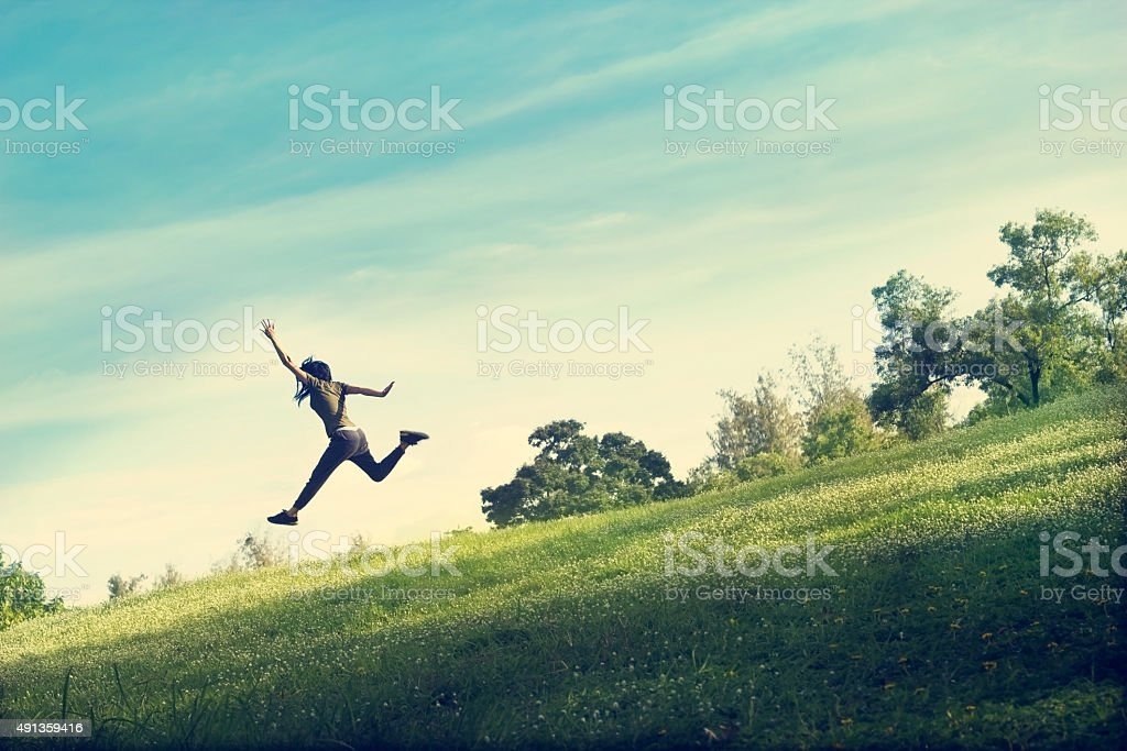 woman running and jumping funny relax on green grass flower stock photo
