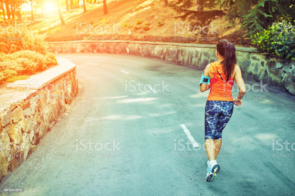 woman running around in the park in the morning stock photo