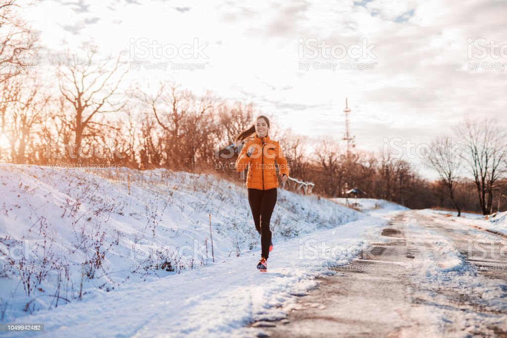Woman running at snowy mountain. stock photo