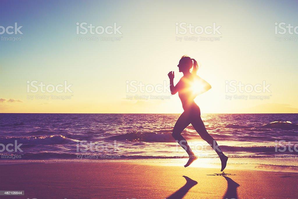 Woman Running at Sunset stock photo