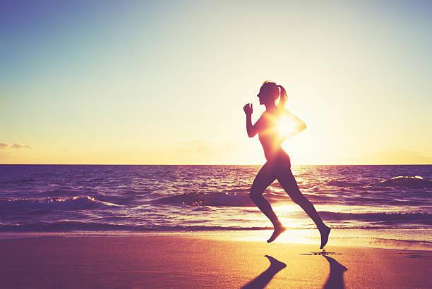 Frau läuft bei Sonnenuntergang – Foto