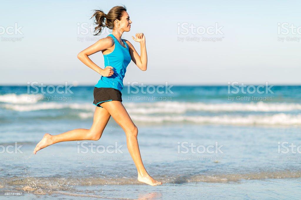 Donna in esecuzione in spiaggia - foto stock