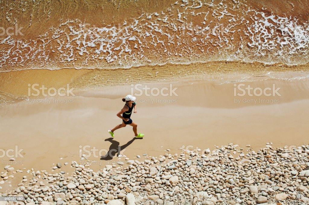 Woman running at the beach stock photo