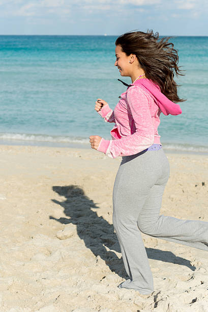 Woman running at the bech stock photo
