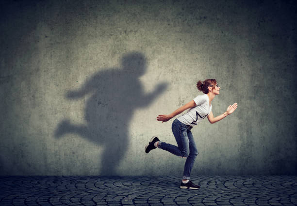 Woman running away from her fat shadow on the wall stock photo