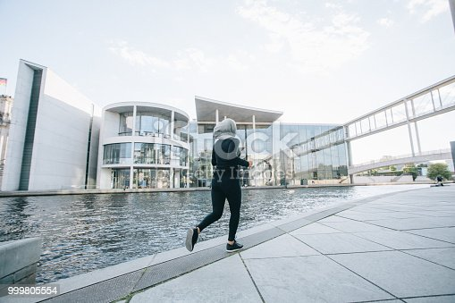 istock Woman running by the river 999805554