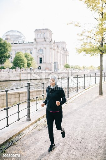 istock Woman running by the riverside 999805678