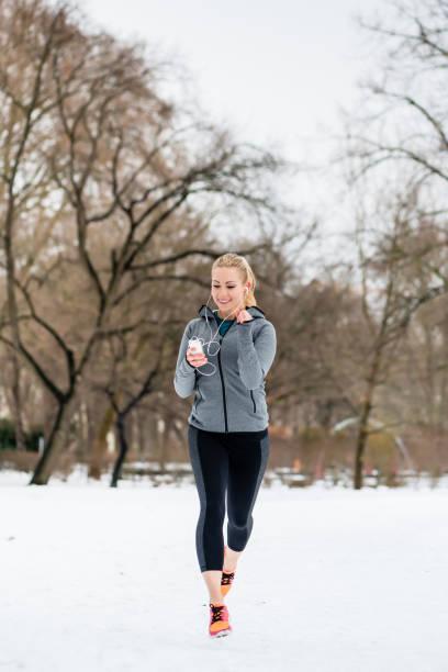 Mujer que corre por un camino en día de invierno en el Parque - foto de stock