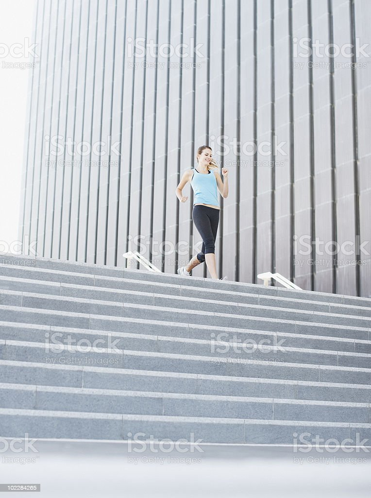 Woman running down urban staircase royalty-free stock photo