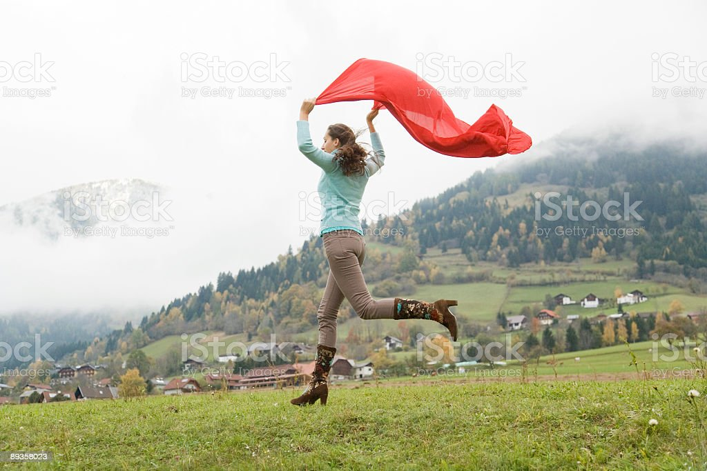 Woman running downhill in mountains holding red scarf to wind royalty-free stock photo