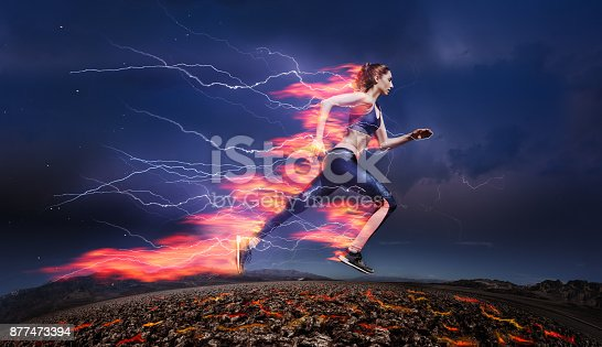 Side view of sporty woman running fast against stormy sky with lightning and tongues of flame