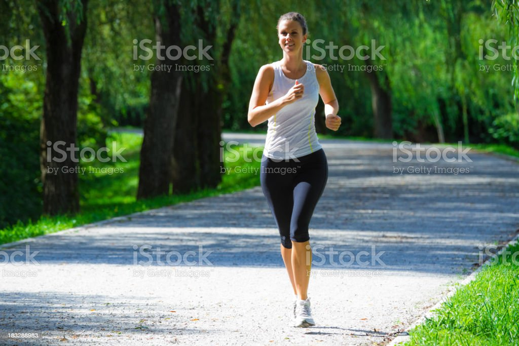 Woman running in a city park for exercise royalty-free stock photo