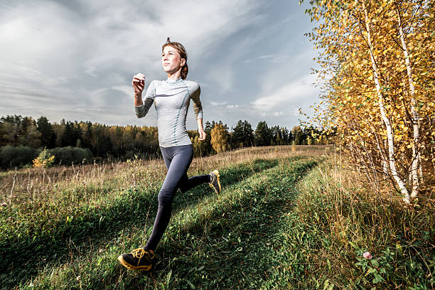 woman running in autumn forest - trail running fotografías e imágenes de stock