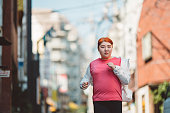 A young Japanese body positive woman is running in the street.