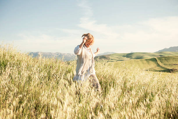 woman running in grassy field - rural lifestyle stock photos and pictures
