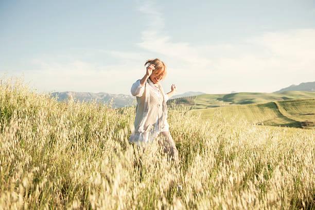 femme courir dans un champ herbeux - mode de vie rural photos et images de collection