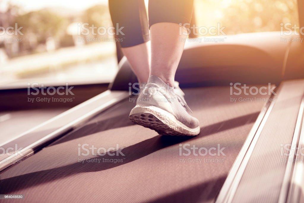 フィットネス ジムでマシン トレッドミルで走っている女性。 - 1人のロイヤリティフリーストックフォト