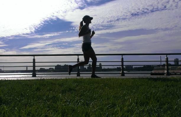 frau läuft im park, new york, usa - nike damen sneaker stock-fotos und bilder