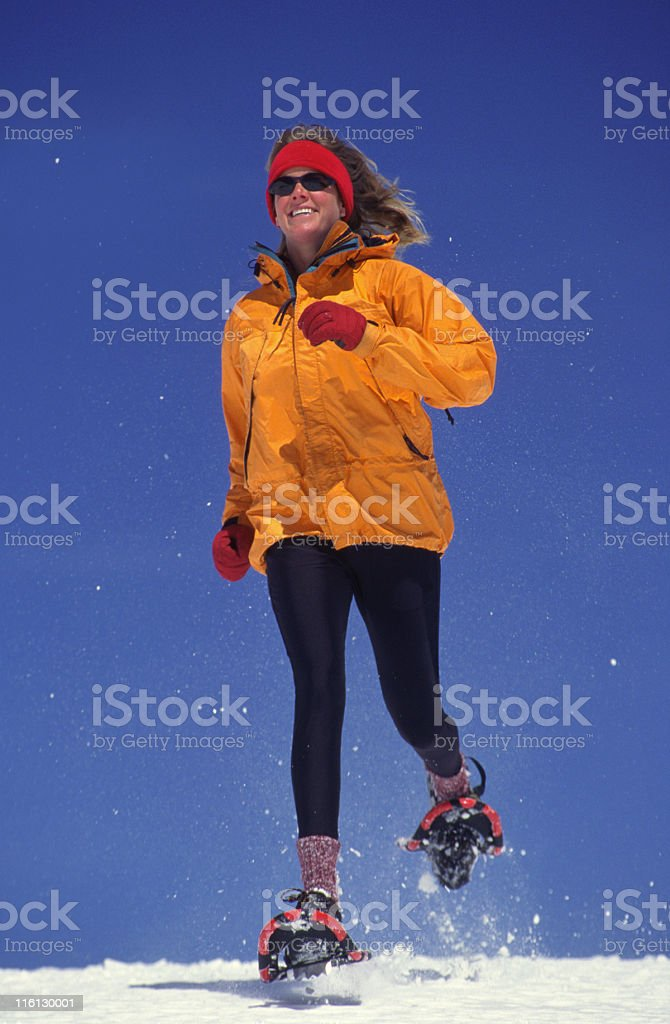 Woman running in snowshoes royalty-free stock photo