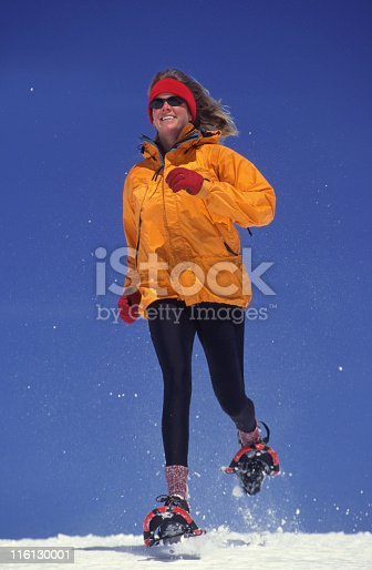 Smiling woman running on snowshoes against blue sky
