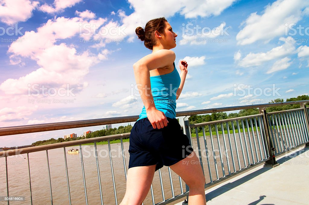 Woman running in the city, by the bridge. stock photo
