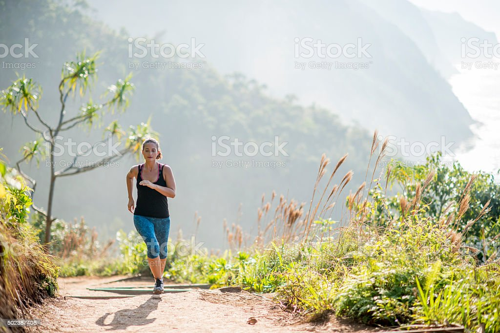 Woman Running in the Hawaiian Mountains stock photo