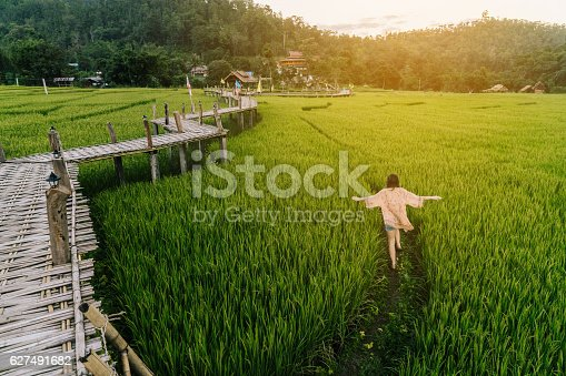 Young Caucasian woman running  in the rice field in Thailand